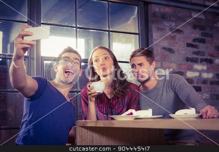 Grimacing friends taking selfies  stock photo, Grimacing friends taking selfies at coffee shop by Wavebreak Media