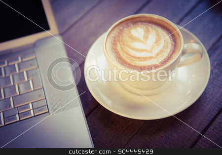 Cup of cappuccino with coffee art next to laptop stock photo, Cup of cappuccino with coffee art next to laptop on wooden table by Wavebreak Media