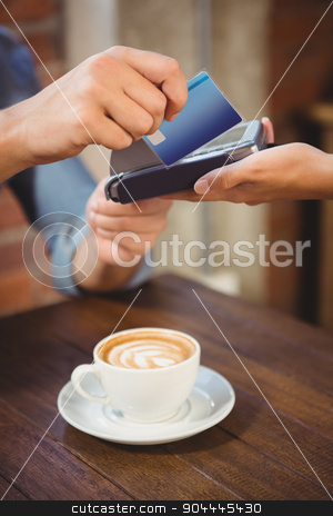Male customer paying with credit card stock photo, Male customer paying with credit card at coffee shop by Wavebreak Media
