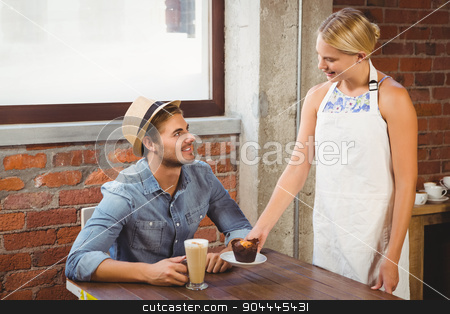 Smiling blonde waitress serving muffin to handsome hipster stock photo, Smiling blonde waitress serving muffin to handsome hipster at coffee shop by Wavebreak Media