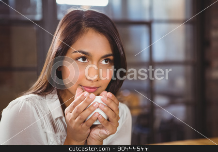 Beautiful woman drinking a coffee and looking away stock photo, Beautiful woman drinking a coffee and looking away in a cafe by Wavebreak Media