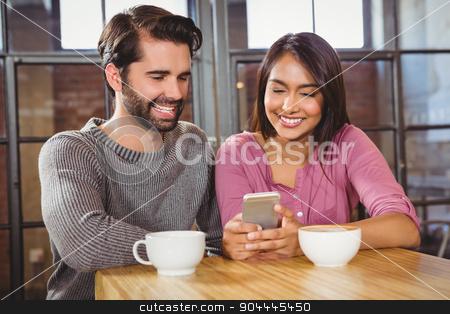 Cute couple looking at a smartphone stock photo, Cute couple looking at a smartphone at a cafe by Wavebreak Media