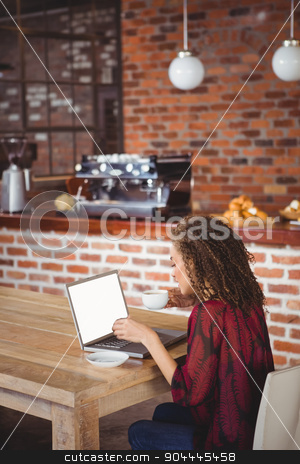 Pretty brunette having coffee using laptop stock photo, Pretty brunette having coffee using laptop at the cafe by Wavebreak Media