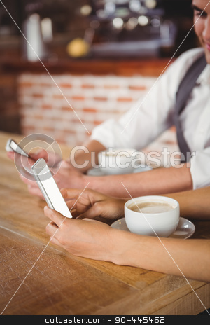 Cute couple sitting in cafe looking at smartphone stock photo, Cute couple sitting in cafe looking at smartphone on a sunny day by Wavebreak Media