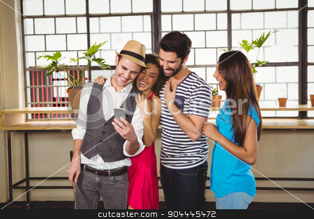 Group of friends looking at a smartphone stock photo, Group of friends looking at a smartphone in a cafe by Wavebreak Media