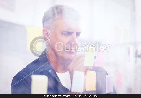 Casual businessman writing on post its stock photo, Casual businessman writing on post its stuck on the wall at office by Wavebreak Media