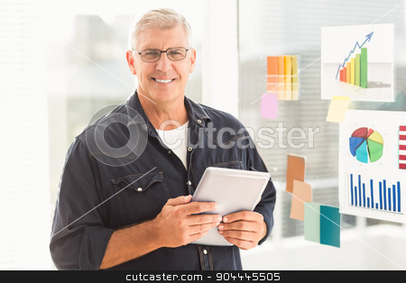 Smiling businessman holding a digital tablet stock photo, Portrait of a happy businessman holding a digital tablet at office by Wavebreak Media
