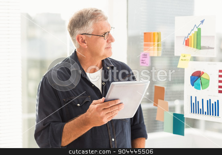 Attentive businessman looking flow charts on the wall stock photo, Attentive businessman looking flow charts on the wall at office by Wavebreak Media