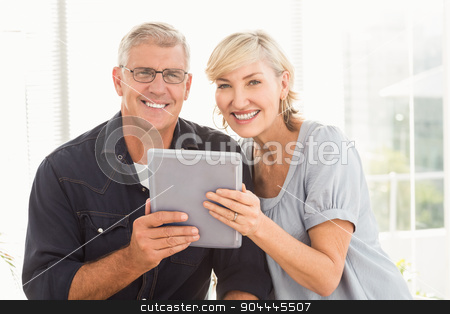 Smiling business team working over a tablet stock photo, Portrait of a smiling business team working over a tablet at office by Wavebreak Media