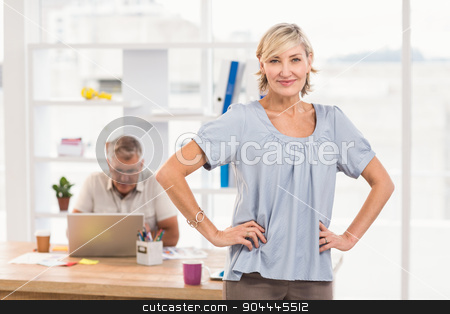 Smiling businesswoman with hands on hips stock photo, Portrait of a smiling businesswoman with hands on hips at office by Wavebreak Media