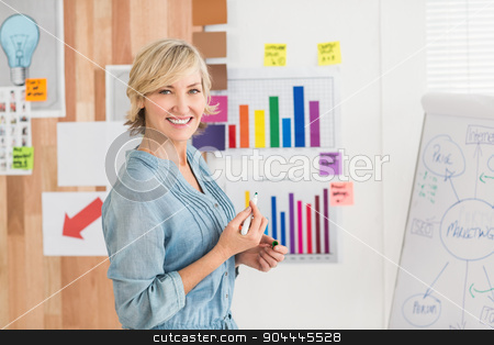 Smiling businesswoman writing on a white board stock photo, Portrait of a smiling businesswoman writing on a white board at office by Wavebreak Media