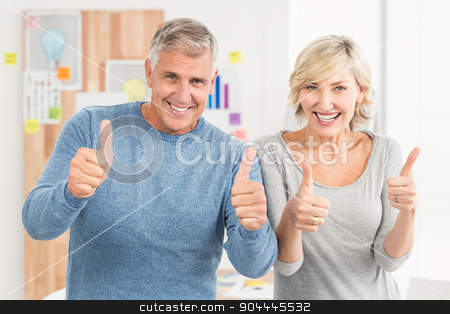 Smiling business team gesturing thumbs up stock photo, Portrait of a smiling business team gesturing thumbs up at office by Wavebreak Media