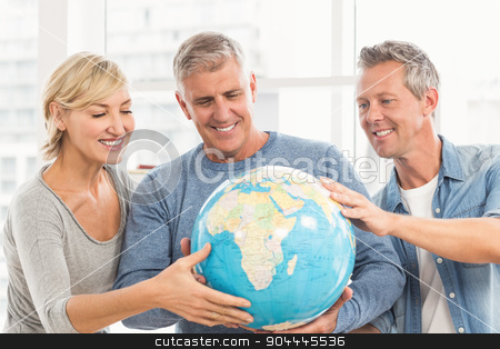 Happy business colleagues holding terrestrial globe stock photo, Happy business colleagues holding terrestrial globe at office by Wavebreak Media