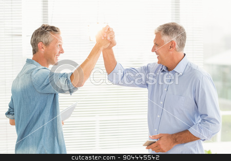 Smiling business colleagues giving high-five stock photo, Smiling business colleagues giving high-five at the office by Wavebreak Media