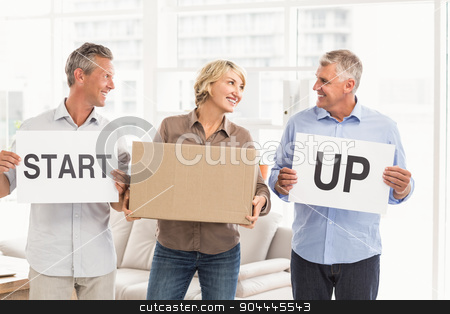 Smiling casual business people holding start up sign stock photo, Smiling casual business people holding start up sign in the office by Wavebreak Media