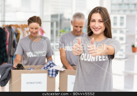 Smiling female volunteer doing thumbs up stock photo, Portrait of smiling female volunteer doing thumbs up in the office by Wavebreak Media