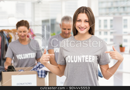 Smiling female volunteer pointing on shirt stock photo, Portrait of smiling female volunteer pointing on shirt in the office by Wavebreak Media