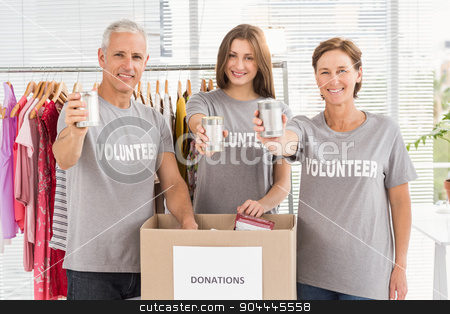Smiling volunteers showing donated cans stock photo, Portrait of smiling volunteers showing donated cans in the office by Wavebreak Media