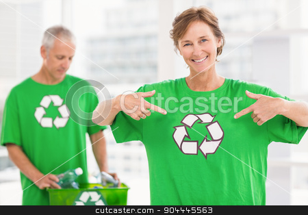 Smiling eco-minded woman showing her recycling shirt stock photo, Portrait of smiling eco-minded woman showing her recycling shirt in the office by Wavebreak Media