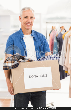Smiling casual businessman holding donation box stock photo, Portrait of smiling casual businessman holding donation box in the office by Wavebreak Media