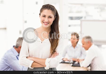 Smiling pretty businesswoman in front of colleagues stock photo, Portrait of smiling pretty businesswoman in front of colleagues in the office by Wavebreak Media