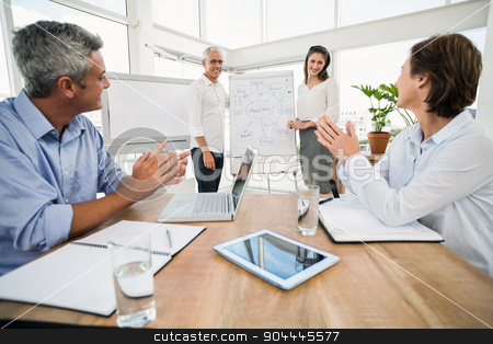 Smiling business colleagues ending presentation stock photo, Smiling business colleagues ending presentation in the office by Wavebreak Media
