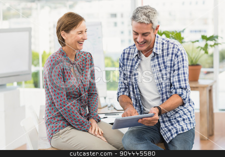 Smiling casual business colleagues using tablet stock photo, Smiling casual business colleagues using tablet in the office by Wavebreak Media