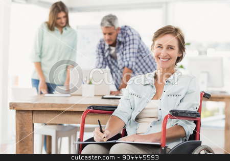 Casual businesswoman in wheelchair with notepad stock photo, Portrait of casual businesswoman in wheelchair with notepad in the office by Wavebreak Media
