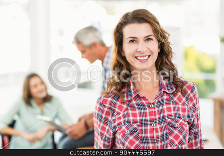 Casual female artist with colleagues in background at office stock photo, Portrait of a casual female artist with colleagues in the background at a bright office by Wavebreak Media