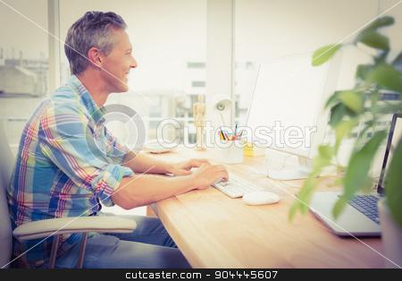 Smiling casual designer using computer stock photo, Smiling casual designer using computer in the office by Wavebreak Media