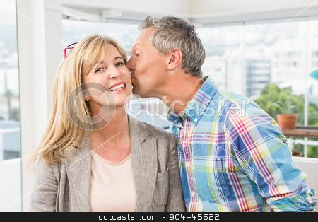 Casual designer giving his colleague kiss on cheek stock photo, Portrait of casual designer giving his colleague kiss on cheek in the office by Wavebreak Media
