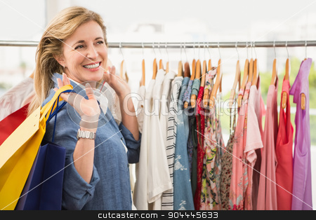 Smiling woman with shopping bags stock photo, Smiling woman with shopping bags in clothing store by Wavebreak Media