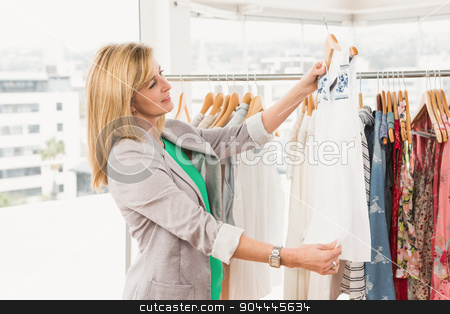 Smiling woman browsing clothes stock photo, Smiling woman browsing clothes in clothing store by Wavebreak Media