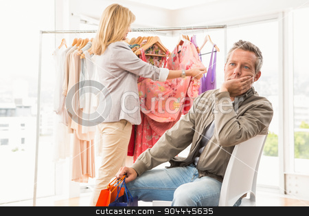 Bored man waiting for his shopping woman stock photo, Bored man waiting for his shopping woman in clothing store by Wavebreak Media