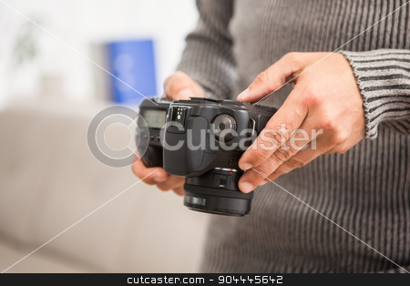 Close up view of hands holding camera stock photo, Close up view of hands holding camera in the office by Wavebreak Media