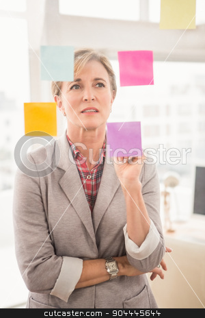 Casual businesswoman reading sticky notes stock photo, Casual businesswoman reading sticky notes in the office by Wavebreak Media