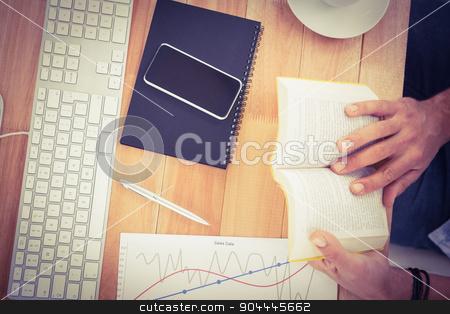 Businessman reading book on wooden desk stock photo, Businessman reading book on wooden desk in the office by Wavebreak Media