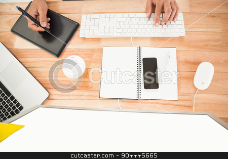 Hands working with computer and digitizer stock photo, Hands working with computer and digitizer on wooden desk by Wavebreak Media