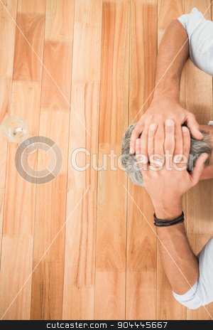 Overworked casual businessman leaning on wooden desk stock photo, Overworked casual businessman leaning on wooden desk in the office by Wavebreak Media