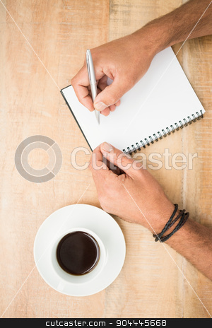 Hands writing on notepad stock photo, Hands writing on notepad on wooden table by Wavebreak Media