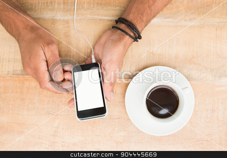 Hands holding smartphone next to cup of coffee stock photo, Hands holding smartphone next to cup of coffee on wooden desk by Wavebreak Media
