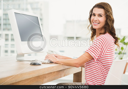 Smiling casual businesswoman working with computer stock photo, Portrait of smiling casual businesswoman working with computer in the office by Wavebreak Media