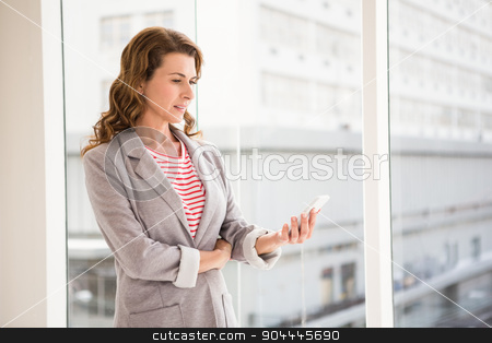 Casual businesswoman using smartphone stock photo, Casual businesswoman using smartphone in the office by Wavebreak Media