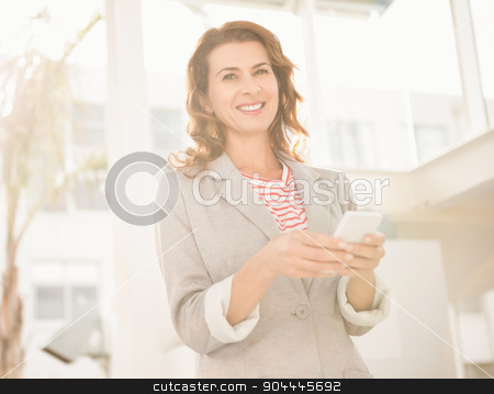 Smiling casual businesswoman holding smartphone stock photo, Portrait of smiling casual businesswoman holding smartphone in the office by Wavebreak Media