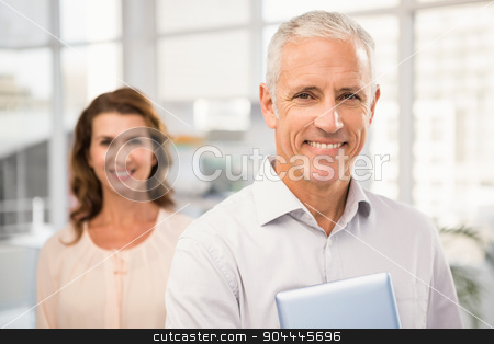 Casual business colleagues smiling at camera stock photo, Portrait of casual business colleagues smiling at camera in the office by Wavebreak Media