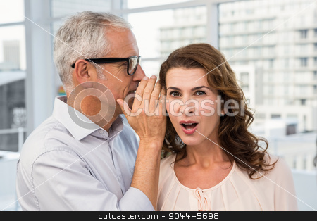 Casual businessman whispering secret to his colleague stock photo, Casual businessman whispering secret to his colleague in the office by Wavebreak Media