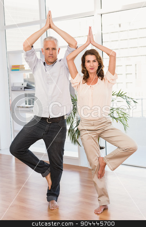 Peaceful casual business colleagues doing yoga stock photo, Portrait of peaceful casual business colleagues doing yoga in the office by Wavebreak Media