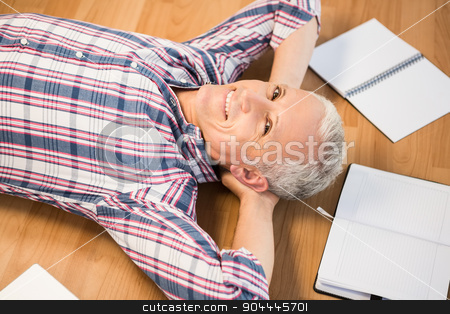 Smiling man lying on floor surrounded by office items stock photo, Portrait of smiling man lying on floor surrounded by office items  by Wavebreak Media