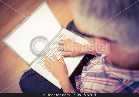 Casual man sitting and working with laptop stock photo, Casual man sitting and working with laptop on wooden floor by Wavebreak Media
