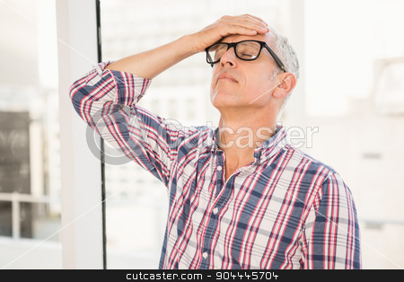 Troubled casual businessman leaning against window stock photo, Troubled casual businessman leaning against window in the office by Wavebreak Media
